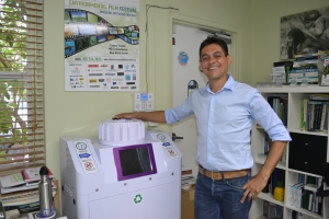 Rodrigues ao lado de um aparelho de reciclagem na sala da ECOMB. Foto de Carla Guarilha
