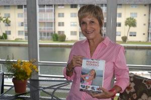 Heloisa, na casa de Eddie, em Miami, mostra com orgulho a capa do livro. Seu pai biológico morreu quando ela tinha 4 anos. Foto de Carla Guarilha
