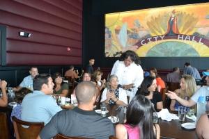 Epps anima uma mesa de brasileiros e conversa com dona Yedda Paradela, carioca, em Miami desde 1959, que comemorava seus 84 anos com a família no City Hall. Foto de Carla Guarilha