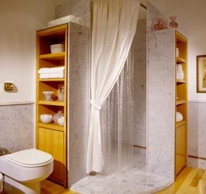 A cortina de plástico americana no banheiro de mármore fez enorme sucesso, dando inicio a sua marca registrada: simplicidade com sofisticação. Foto cortesia de Camilla Matarazzo