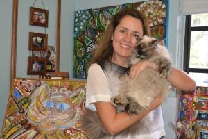 Viviane com Samantha Jones, sua gata, ao lado de um de seus quadros. Ela tem um pequeno atelier em casa e ainda sonha em abrir uma galeria de arte em Miami. Foto de Carla Guarilha