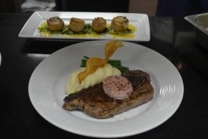Prime N.Y Strip, um dos favoritos no menu, e atrás, vieiras com toque de caviar